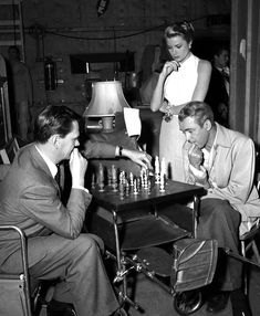 REAR WINDOW (1954) - Jimmy Stewart, Grace Kelly and Wendell Corey enjoy a game of chess between scenes - Directed by Alfred Hitchcock - Paramount - Publicity Still.