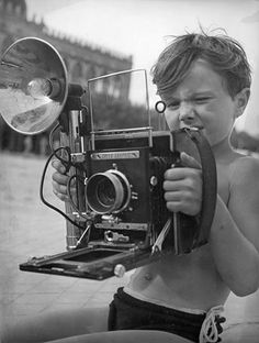 kid with an OLD camera. Love the look on his face. I feel like that with my camera sometimes too:)