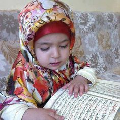 A lil muslim girl, reading a verse of Quran.