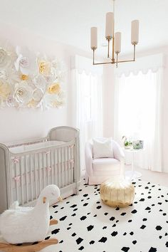 Baby Girl Nursery with soft blush tones and charming swan décor and a paper…