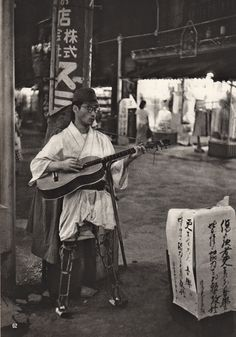 A former soldier begging in the streets, Asakusa, Tokyo, 1951 by Werner Bischof.  Many wounded soldiers were forced into poverty after the war, since the government did not allow them any pension.