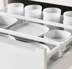 Detalle de un cajón abierto en una cocina de IKEA. Vajilla blanca ordenada dentro de su cajón.