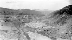 Reservoir in San Francisquito Canyon that held 12.5 billion gallons of water for the Los Angeles Department of Water and Power — seen here just after the collapse of the St. Francis Dam on March 12-13, 1928. The line between dark and light represents the pre-disaster water level. The concrete dam would have been just out of view at the bottom of this photo.