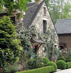 Stone cottage style home near Atlanta, Georgia. Landscape architect Richard Anderson included a profusion of climbing roses clinging to the stone facade and cascading over the covered entry way. Fairytale Cottage, Storybook Cottage, Garden Cottage, Cute Cottage, Cottage Style Homes, Cottage Design, Cottages Anglais, Stone Facade, Stone Houses
