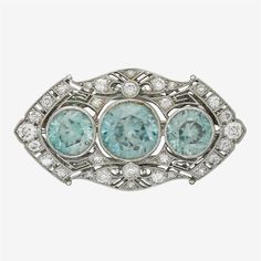 An Art Deco zircon, diamond and platinum brooch<z> <br /> set with three round-cut zircons and accented by single and old mine-cut diamonds; total diamond weight approximately: 1.10 carats. <br /> <br /> Gross weight: 7.0 dwt.; Length: 1.5 in. <br />