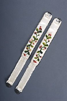 Pair of Ladies Embroidered Garters  French, ca. 1800    Concealed under full-length gowns and petticoats, garters secured the stockings just above or below the knee.  In the latter part of the eighteenth century, short garters incorporating fine metal springs and buckles replaced long ribbons or bands that tied around the leg.
