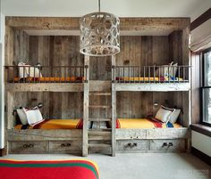 Rustic country bunk room features built-in barnwood bunk beds dressed in yellow bedding flanking a rustic bunk bed ladder illuminated by a wood geometric drum pendant.