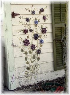 Old faucet handles painted and mounted on wall as flowers