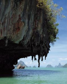 Hidden Sea Caves in Phang Nga, Thailand.  Dramatic limestone karsts topped by a veil of lush green vegetation jut out of the ocean, and the only sign of life is the occasional gang of scampering monkeys.