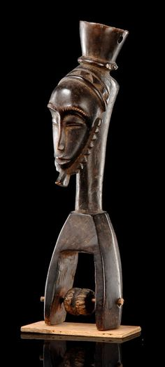 Africa | Heddle pulley with mask face from the Guro people of the Ivory Coast | Wood, with blackish brown patina