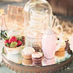 We love this shoot! It's a super whimsical and elegant dinner party styled shoot, but also fun and summery feeling. The soft pastel pink colored tea pot, plates, and canisters arrange well with all the flowers. Overhead, two chandeliers hang from tree branches to lend a classy feeling to the event. The Collective Photographers were …