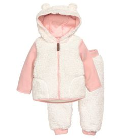 White/light pink. Jacket and pants in soft pile. Jacket with jersey-lined hood with attached ears, contrasting fleece sleeves, zip at front, and side