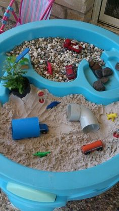 Fun table (sensory table) Borrowed table from Mons Playgroup centre free toy library, but you could use perhaps washing up tub, storage tub- use your imagination and the possibilities are endless:) sand, some  pebbles, some old piping (but again u could use all sorts old plastic food tubs, small box etc.) for little tunnels, 2 mini ferns (a variation could be using herbs, or flowers) some big pebbles found in our garden, sand, & I raided the kids toys to find cars & dinosaurs :)