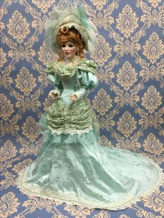 """MINT JULEP. A magnificent example of the dollmaker's art, crafted from head to toe in fine bisque porcelain. Completely jointed, with sparkling hand-set paperweight glass eyes. Lavishly costumed in mint green satin jacquard, iridescent organza and elegant corded lace. Adorned with sparkling sequins and shimmering faux pearls. Wearing a spectacular matching hat and carrying a fashionable feathered fan. From Maryse Nicole's Premiere Signature Collection.   Approximately 21"""" (53 cm) in height."""