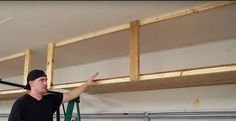 Create a Garage Door Storage System  Chances are your garage is filled to the brim with stuff you hardly use. Get that stuff off the floor and into plastic totes on the ceiling! In one afternoon you can build a sliding carriage from 2×4's in the space between your ceiling and the garage door.