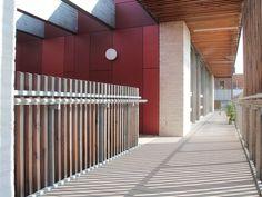 Modernes Schulgebäude mit umlaufendem Balkon mit grauen WPC Dielen
