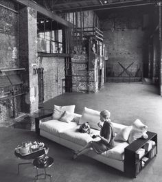 this is basically my dream life, not gonna lie. industrial loft, exposed brick, huge couch with bookshelf arms, adorable bulldog