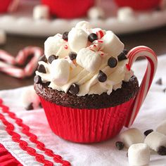 """Mmmm. This little beauty is a hot cocoa cupcake (an extra-rich chocolate cupcake, made with hot cocoa instead of water!) with all your favorite traditional hot cocoa toppings: whipped cream, marshmallows, mini chocolate chips, and crushed candy canes. The mini candy cane """"handle"""" is the ..."""