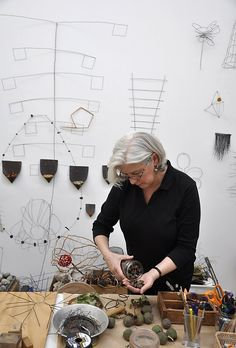 Mari Andrews Acorns appear to dance on the edges of layered, circular wire; twisted, braided tree moss erupts into a twirl and tiny leaves adorn paper. There are heftier versions too; wires formed into a spider web enveloping a speckled stone, alphabet pasta adorning a magnolia leaf and an oval sculpture of lichen and w...