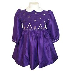 """Annabel (Long Sleeved) - Traditional smocked dress with embroidery overlay.  Styled with long sleeves and """"Peter Pan"""" collar. Button cuffs to sleeves. Button fastening at the back, with matching fabric """"ribbons"""" to tie a bow.  Fabric piping to collar and cuffs to compliment embroidery. Available in sizes 6 months - 8 years."""