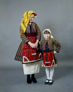 """Mother and child with a quilted """"anteria"""" coat and jacket of the Skopiá, Florina group of villages in Macedonia."""