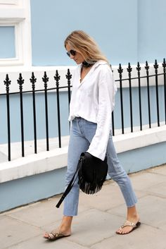Cropped raw hem jeans with a white blouse, sandals, fringe bag. | HarperandHarley