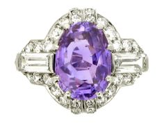 Art Deco purple sapphire and diamond ring by Ellis Bros, Toronto, circa 1920. A platinum ring vertically set with one central oval old cut natural purple sapphire in a claw setting with an approximate weight of 5.00 carats, flanked by two horizontal baguette cut diamonds in rubover settings with an approximate total weight of 0.80 carats, all encircled by a single row of twenty two round old cut diamonds in millegrain bead settings with an approximate total weight of 1.00 carats, this border ...