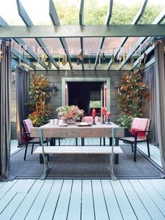 The space below the pergola is perfect for casual, alfresco dining. The simplistic decor features a modern table and an eclectic mix of seating, including a weathered, wooden bench.