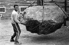 At his training camp cabin, Ali pushes a boulder during a photo shoot in Deer Lake, Penn., in August 1973. Ali was training for his rematch against Ken Norton, who broke his jaw five months earlier.