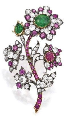 An Antique Silver-Topped Gold, Ruby, Emerald and Diamond Brooch. Designed as a floral spray with the largest flowerhead set en tremblant, centring an oval-shaped emerald, with a bud set with a pear-shaped emerald, an additional flowerhead set with a round ruby, further set with round, old mine and cushion-cut rubies, accented by round, pear, old mine and square-cut diamonds; mid-19th Century. #antique #Victorian #brooch