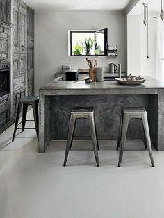 reforma cocina, isla central de obra con barra y acabado microcemento, armario empotradro con puertas de madera reutilizada.