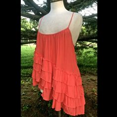 Free People coral Flutter Tiered Ruffled tank top FABULOUS FREE PEOPLE CORAL ( TOMATO) ASYMMETRICAL HI LO RUFFLED & TIERED CRISS CROSS STRAP FLUTTER SWINGY TOP                                 Ruffled tiers and an asymmetrical hem make this Free People top a boho-chic pick for pretty spring style! Rayon Machine washable Imported Scoop neckline Sleeveless, spaghetti straps Ruffled tiers through body Asymmetrical hem Pullover style Hits at the hip NEW WITH TAGS  *  SIZE:  X  SMALL retail price…