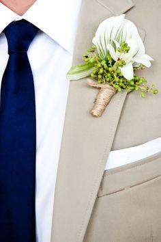 Trajes de novio modernos en color caramelo para novios modernos. Ideales para bodas formales de jardín. Detalles para novio: corbata en azul marino, pañuelo en el bolsillo y boutoniere de flores frescas y naturales.