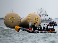 """Rescue workers operate near floats where the capsized passenger ship """"Sewol"""" sank, during the rescue operation in the sea off Jindo, South K..."""