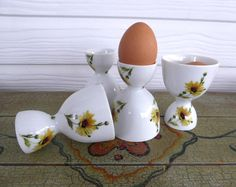 This is a a set of 4 English double egg cups in a pretty yellow Daisies pattern in bone china made in the 1970s by an unknown maker. The eggcups each measures 4 inches high by 2.85 inches in diameter