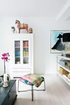 I love the dark table as a contrast w/ everything white in the room.  Also, great bookcase, pink flowers, everything!