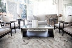 Chic, angled living room features matching black spool chairs upholstered in platinum gray leather facing each other across from an art deco mirrored coffee table atop a gray herringbone rug.