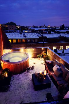 Inviting winter rooftop with hot tub. Place pillows and blanket in the dryer for a few minutes before going outside so they will be nice and toasty.