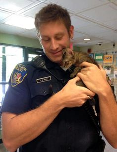 Real men love cats. A tiny stray kitten found a Baltimore police officer to be his human dad for life.