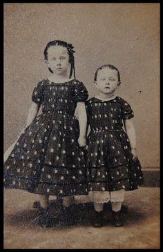 Previous pinner states this is a Momento Mori of sisters held up by support stands. I do not believe this to be a post-mortem photo at all. Both sisters are looking directly at the camera. Two things to be very wary of: Claimed momento mori where the body is standing, or is looking at the camera. You can be almost 100% certain you are NOT looking at a postmortem photo. What do you think about these two children?