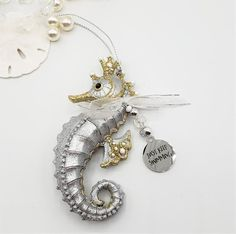 """Beach Christmas seahorse ornament. Beautiful coastal nautical Christmas ornament, this adorable resin sea horse is decked out for the holidays with a little bow and a crystal beaded charm dangle, the charm reads """"Just Keep Swimming"""".  This seahorse ornament comes in two very slightly different styles, we'll assort. He beautifully coordinates with our sand dollar and starfish ornaments too!   Measures 4"""" tall."""