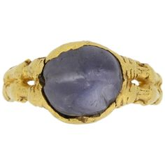 Medieval Zoomorphic Sapphire Gold Ring.  An important piece, horizontally set with a sapphire cabochon, originally used as a bead with lengthwise drill hole, in a closed back collet setting, bezel gripped either side by two pairs of gaping mouths of animals, possibly dragons, with their bodies flowing round the band, their forelegs outstretched towards their heads, their hindlegs swallowed by gaping snakes whose tails intertwine to form the rest of the band, circa 12th - 14th century.