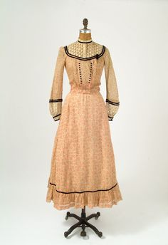 Summer day dress, ca. 1890s. Coral feedsack cotton print with black velvet trim, with openwork eyelet cotton on yoke collar and cuffs and decorative black velvet-covered buttons. Two pieces; bodice opens with hooks at front yoke and down side of front panel. Skirt is a bustle, gathered in back, and lined in muslin. missfarfalla/etsy