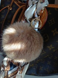 Add an element of uptown sophistication to your favorite handbag with a lush faux-fur bag charm accented with gold tone hardware. Highest quality faux fur