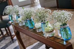 The Registrars Table was dressed with blue Mason Jars were filled with posies of Gypsophilia, small jars and vessels were placed in between each one containing a posy of