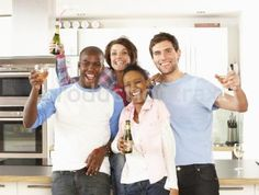 Royalty Free Stock Photos at Productiontrax.com | Group Of Young Friends Enjoying Drink In Modern Kitchen