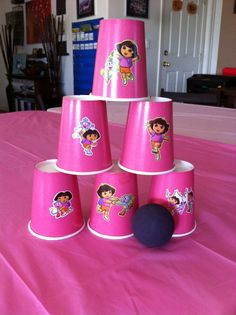 DIY Dora the Explorer party game made with paper cups, Dora stickers, and racquetball to knock down the cups.