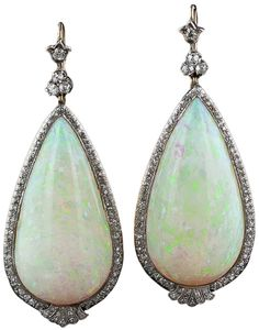Antique 90.00 Carats Opal and Diamond Dangle Earrings.     Edwardian.   A perfectly matched pair of pear shape drops, each weighing 45.00 carats - 90 carats total! - are delicately framed in platinum over 18 karat gold with tiny twinkling diamonds. The colorful gemstones display an iridescent palette of pastel green, blue and peach colors and are surmounted by sparkling trefoil diamond tops. Lang Antiques.