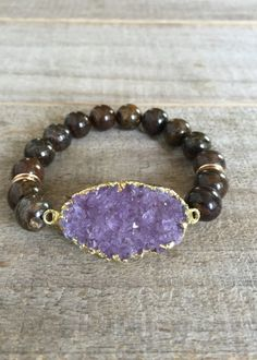 Glittering amethyst druzy is adorned with smooth round bronzite beads along this stretch bracelet. Beautiful oval shaped druzy is 100% natural, meaning it has not been color treated or enhanced in any way. It measures 1 1/4 wide (not including side loops) x 5/8 tall and features gold electroplating along the side walls - the back is left natural to allow light to pass through. It is a beautiful shape and color with amazing sparkle. Surrounding bronzite beads are a flecked brown color and…
