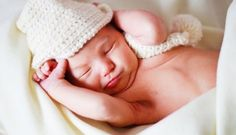 This is a cute newborn baby who wears a white hat and enjoying his/her sleeping.